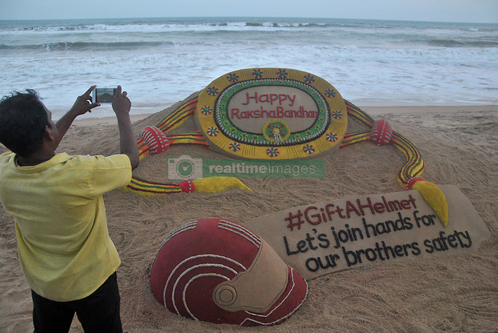 """August 6, 2017 - Puri, Orissa, India - A visitor taking pictures of a sand art, creating by sand artist Sudarshan Pattnaik on the eve of Indian Hindu festival """"Rakha Bandhan"""" at the Bay of Bengal Sea's eastern coast beach at Puri, 65 km away from the eastern Indian state Odisha's capital city Bhubaneswar. """"Rakhya Bandhan"""" is a festival in India every un married girls ties threads into their brother's hand for their safety in the society. (Credit Image: © Str/NurPhoto via ZUMA Press)"""
