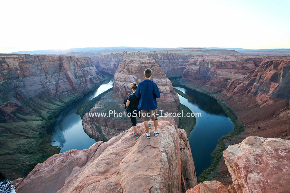 Hikers admire the view at Horseshoe Bend Colorado River Arizona USA