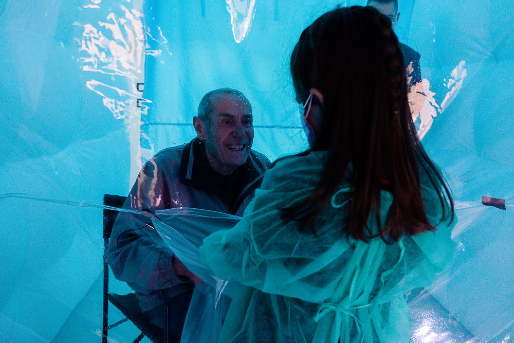 A girl wearing a protective suit against the spread of the novel coronavirus COVID-19 meets her grandfather through a plastic sheet installed in a special 'hug room' organised to keep people safe from COVID-19 infection at a care home in Santa Lucia di Serino, province of Avellino, southern Italy, on January 2, 2021.