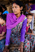 Lakshmi Tharu (in purple), 22, sits with her younger of 2 sons (right) aged 10 and 4 as she gathers with other child mothers and child brides to see Pahari Tharu, 52, the female community health worker in Bhaishahi village, Bardia, Western Nepal, on 29th June 2012. Lakshmi has never been to school and was married to an 11 year old boy when she was nine, giving birth to her first child when she was 12. In Bardia, StC works with the district health office to build the capacity of female community health workers who are on the frontline of health service provision like ante-natal and post-natal care, and working together against child marriage and teenage pregnancy especially in rural areas. Photo by Suzanne Lee for Save The Children UK