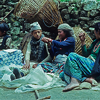 Lowland Nepalis relax as they wait for Sherpa customers to buy goods they have carried for several days to the Saturday market at Namche Bazaar in Nepal's Himalaya.