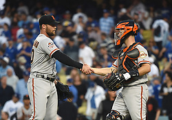 March 29, 2018 - Los Angeles, CA, U.S. - LOS ANGELES, CA - MARCH 29: San Francisco Giants Pitcher Hunter Strickland (60) and San Francisco Giants Catcher Buster Posey (28) celebrate the victory during the MLB opening day game between the San Francisco Giants and the Los Angeles Dodgers on March 29, 2018 at Dodger Stadium in Los Angeles, CA. (Photo by Chris Williams/Icon Sportswire) (Credit Image: © Chris Williams/Icon SMI via ZUMA Press)