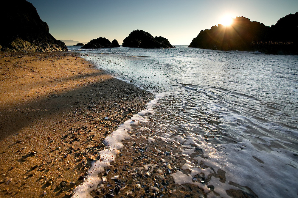 Sunset and blue skies over small rugged lava rock islands, surrounded by soft yellow sand, off the main island of Anglesey, North Wales.