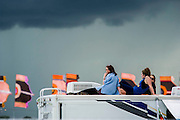 Peopel listen to Haim fronm the top of a camper van as the storm clouds gather again. The 2014 Glastonbury Festival, Worthy Farm, Glastonbury. 27 June 2013.  Guy Bell, 07771 786236, guy@gbphotos.com
