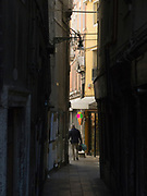 Narrow Venice street with man carrying shopping bags walking past a colorful ice cream cone sign