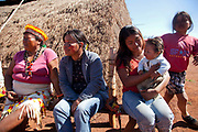 Guarani women and family sitting on a bench, watching a traditional dance. The Guarani are one of the most populous indigenous populations in Brazil, but with the least amount of land. They mostly live in the State of Mato Grosso do Sul and Mato Grosso. Their tradtional way of life and ancestral land is increasingly at risk from large scale agribusiness and agriculture. There have been recorded cases and allegations of violence between owners of large farms and the Guarani communities in this region.