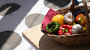Basket of ingredients for a Greek meal on a table with the classic Santorini stone walkway in the background