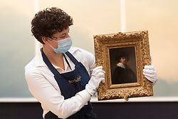 © Licensed to London News Pictures. 23/07/2020. London, UK. A Sotheby's staff member holds a painting titled self portrait, wearing a ruff and black hat painting (1632) by artist Rembrandt Van Rijn with an estimate of £12-16 million. Works spanning over half a millennium of art history go on display at Sotheby's London ahead of a one-off auction on July 28. Titled 'Rembrandt to Richter', the sale will offer the very best from Old Masters, Impressionist & Modern Art, Modern & Post-War British Art and Contemporary Art – travelling from the Italian Renaissance through to Pop Art. Photo embargoed for usage until 24th July 2020 09:00. Photo credit: Ray Tang/LNP