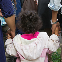 Illegal migrant girl from Afghanistan holds the hands of her parents as they get on a bus under police custody near border town Asotthalom (about 190 km South-East of capital city Budapest), Hungary on July 16, 2015. ATTILA VOLGYI