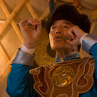 Mongolian Musician Tserendorj plays a mouth harp in his home in Ulaanbaatar, which has decorated to look like a ger (yurt).