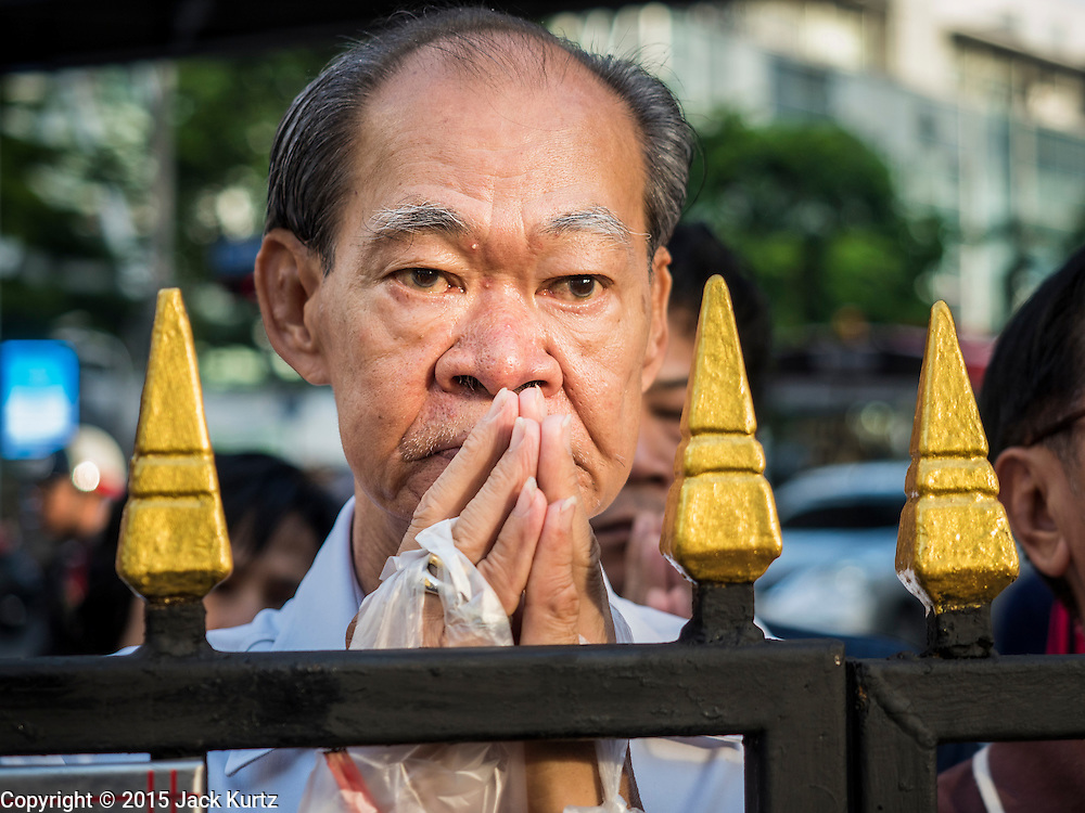"""04 SEPTEMBER 2015 - BANGKOK, THAILAND: A man who couldn't get into the shrine Friday morning prays in front of Erawan Shrine during a special rededication ceremony. A """"Holy Religious Ceremony for Wellness and Prosperity of our Nation and Thai People"""" was held Friday morning at Erawan Shrine. The ceremony was to regain confidence of the Thai people and foreign visitors, to preserve Thai religious customs and traditions and to promote peace and happiness inThailand. Repairs to Erawan Shrine were completed Thursday, Sept 3 after the shrine was bombed on August 17. Twenty people were killed in the bombing and more than 100 injured. The statue of the Four Faced Brahma in the shrine was damaged by shrapnel and a building at the shrine was damaged by debris.     PHOTO BY JACK KURTZ"""