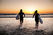 Surfers running into the sea and surf, holding their surfboards, as the sunsets below the horizon line at St Ouen's Bay, Jersey, Channel Islands