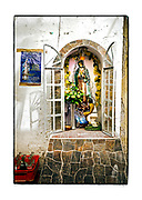 SHOT 2/20/19 10:00:45 AM - A small freestanding capilla outside a food stall in Merida, Mexico. The capilla featured a statue of Our Lady of Guadalupe and various flowers. Passersby left pesos on the statue. Our Lady of Guadalupe is a powerful and ubiquitous symbol of Mexican identity because some guess that Our Lady of Guadalupe's skin tone matches that of Mexico's indigenous population: light brown. She is as much revered for her striking similarity to the vanquished native Mexican population as she is for being the mother of God. Mérida is the capital and largest city in Yucatan state in Mexico, as well as the largest city of the Yucatán Peninsula. As the largest city in the Yucatan it has become a hub for commerce and culture. (Photo by Marc Piscotty / © 2019)
