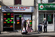 Asian community along Roman Road in East London passes the Roman Empire Chinese takeaway. The borough of Tower Hamlets has a population of 220,000, which includes one of the highest ethnic minority populations in the capital, consisting mainly of Bangladeshis.