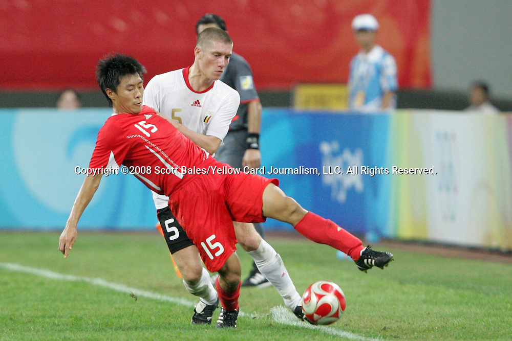 10 August 2008: Jiang Ning (CHN) (15) tries to keep the ball in play in front of Sebastien Pocognoli (BEL) (5).  The men's Olympic soccer team of Belgium defeated the men's Olympic soccer team of China 2-0 at Shenyang Olympic Sports Center Wulihe Stadium in Shenyang, China in a Group C round-robin match in the Men's Olympic Football competition.