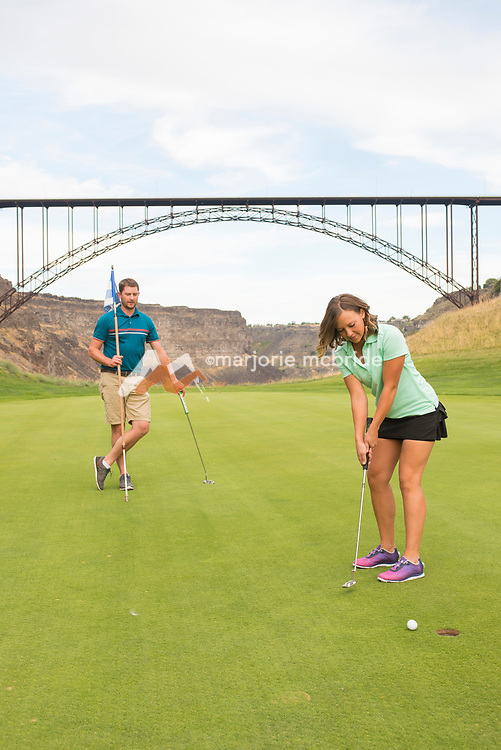 Rudy Ashenbrener left with spouse Sami Ashenbrener right putting on the 4th green with the Perrine Bridge beyond while golfing at Blue Lakes Country Club in the Snake River Canyon of Twin Falls, Idaho.