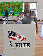 Election judge Joe Avellone sprays disinfectant on voting booth surfaces at the Abraham Lincoln School gym in Belleville on Tuesday November 3, 2020. He said he sprayed down every voting booth periodically, whether they had been used or not.  <br /> Photo by Tim Vizer