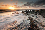 Gale driven waves and foam pile onto Dinas Dinlle shingle beach at sunset, on the North coast of the Llyn Peninsula in North Wales. The large rocks in the image are sea defence measures to stop storm surges pushing the tide over the shingle bar onto the low lying farmland behind.