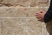 Israel, Jerusalem Old City, A hand gently caresses the Wailing wall model release available