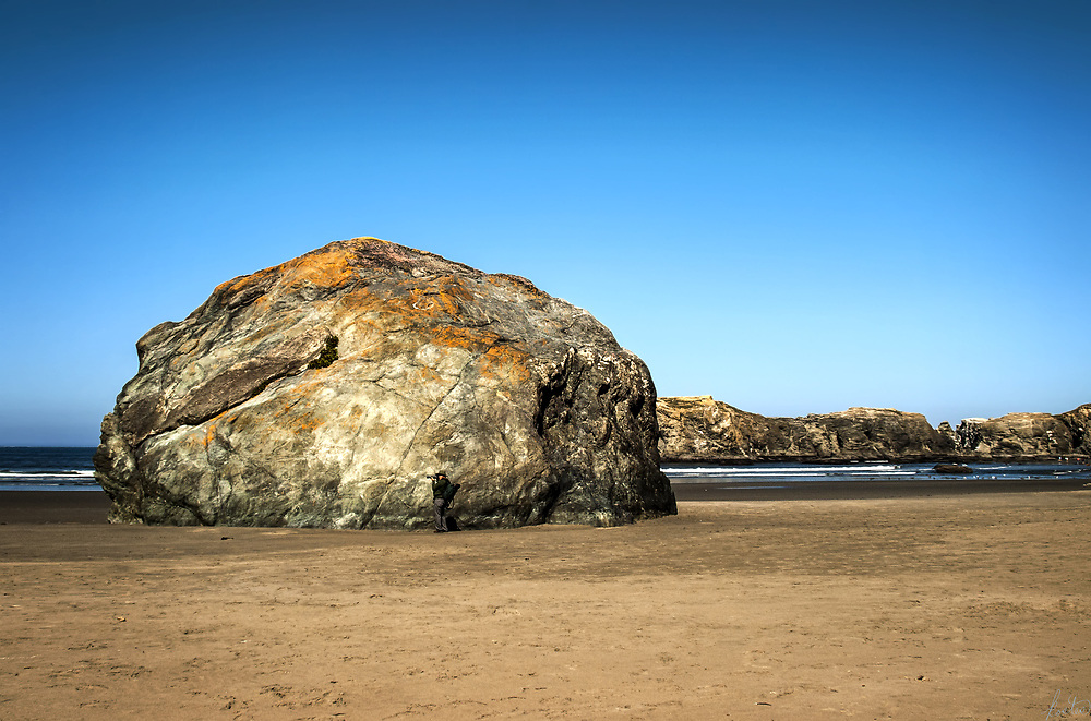 An  image of a large moss covered rock on the shoreline, on the Oregon coast with a photographer standing in front of it, camera to eye.