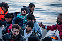 LESVOS, GREECE - FEBRUARY 09: A volunteer holds a young boy after their arrival on a dinghy to a beach in Lesvos from the Turkish coast on February 09, 2015 in Lesvos, Greece. Photo: © Omar Havana. All Rights Are Reserved