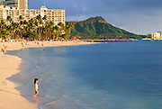 A little girl walking to the ocean on Waikiki Beach with Diamond Head in the background.