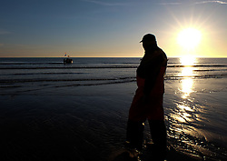 © Licensed to London News Pictures.12/06/15<br /> Saltburn by the Sea, England<br /> <br /> LESLEY JEFFERSON, owner of Ellen, the last remaining commercial fishing boat in Saltburn, walks out to join his boat as dawn breaks over the beach.<br /> <br /> Photo credit : Ian Forsyth/LNP