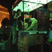 An ice cream vendor near the India Gate park in New Delhi, India. Hundreds of such carts are scattered around the park every night during the summer nights and many people come out for ice cream at 'India gate'.