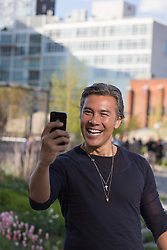 Asian American man enjoying himself by taking a selfie in New York City