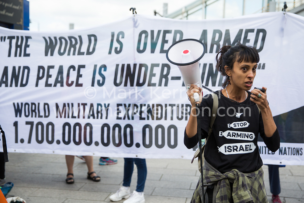 London, UK. 3 September, 2019. Sheila Menon addresses human rights activists protesting outside ExCel London on the second day of a week-long carnival of resistance against DSEI, the world's largest arms fair. The second day's events were organised around a theme of No Faith In War and were attended by representatives of many faith groups including a significant number of Quakers.