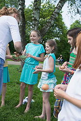 Female trainer distributing eggs to kids for spoon race in a park, Munich, Bavaria, Germany