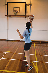 Secondary school student aims for the goal in a game of basketball,