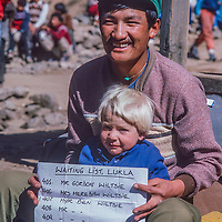 A Sherpa airline agent poses with3-year old Ben Wiltsie at Lukla airstrip in the Khumbu region of Nepal, one of the most dangerous in the world, where flights are commonly delayed or overbooked.