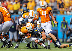 Sep 1, 2018; Charlotte, NC, USA; ennessee Volunteers running back Ty Chandler (8) is tackled by West Virginia Mountaineers linebacker David Long Jr. and West Virginia Mountaineers linebacker Dylan Tonkery (10) during the first quarter at Bank of America Stadium. Mandatory Credit: Ben Queen-USA TODAY Sports