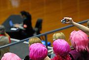 Sporting event spectators in bright wigs, with small digital camera taking photo. Sydney, Australia