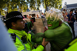 "© Licensed to London News Pictures. 17/09/2019. London, UK. A police officer escorts a protester wearing a ""Hulk"" face mask outside UK Supreme Court in London as the court begins a three day appeal hearing in the multiple legal challenges against the Prime Minister Boris Johnson's decision to prorogue Parliament ahead of a Queen's speech on 14 October. Eleven instead of the usual nine Supreme Court justices will hear the politically charged claim that Boris Johnson acted unlawfully in advising the Queen to suspend parliament for five weeks in order to stifle debate over the Brexit crisis. It is the first time the Supreme Court has been summoned for an emergency hearing outside legal term time. Lady Hale, the first female president of the court who retires next January, will preside. Photo credit: Dinendra Haria/LNP"