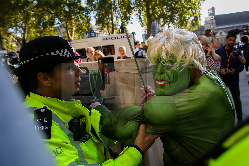 """© Licensed to London News Pictures. 17/09/2019. London, UK. A police officer escorts a protester wearing a """"Hulk"""" face mask outside UK Supreme Court in London as the court begins a three day appeal hearing in the multiple legal challenges against the Prime Minister Boris Johnson's decision to prorogue Parliament ahead of a Queen's speech on 14 October. Eleven instead of the usual nine Supreme Court justices will hear the politically charged claim that Boris Johnson acted unlawfully in advising the Queen to suspend parliament for five weeks in order to stifle debate over the Brexit crisis.It is the first time the Supreme Court has been summoned for an emergency hearing outside legal term time.Lady Hale, the first female president of the court who retires next January, will preside. Photo credit: Dinendra Haria/LNP"""