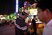 A man wearing a cowboy hat looks at his cellphone at the carnival grounds of the Qingdao (Tsingtao) Beer Festival in Qingdao, China on 27 August, 2011. Named after the locally brewed Tsingtao Beer, one of China's most famous exports, the festival has grown from a local binge drinking feast to an internationally known festival.