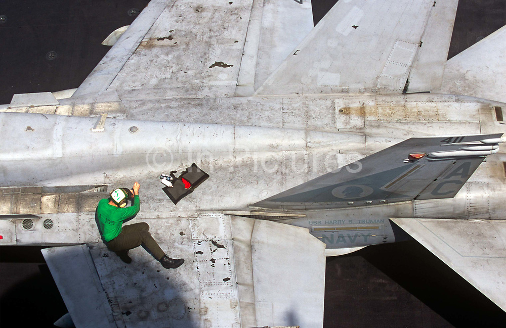 A lone deck hand sailor maintains the grubby surfaces of an F/A-18C Hornets fighter jet on the aircraft carrier USS Harry S Truman.Launched on 7 September 1996 and costing US$4.5 billion, the Truman (CVN-75) is the eighth Nimitz-class supercarrier of the United States Navy, named after the 33rd President of the United States, Harry S. Truman. The Truman is the largest of the US Navy's fleet of new generation carriers, a 97,000 ton floating city with a crew of 5,137, 650 are women.