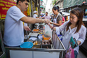 11 SEPTEMBER 2013 - BANGKOK, THAILAND:  A woman buys an order of curry to go from a stand in the Chinatown section of Bangkok. Thailand in general, and Bangkok in particular, has a vibrant tradition of street food and eating on the run. In recent years, Bangkok's street food has become something of an international landmark and is being written about in glossy travel magazines and in the pages of the New York Times.        PHOTO BY JACK KURTZ