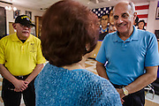 02 AUGUST 2012 - PHOENIX, AZ: Dr RICHARD CARMONA (blue shirt) talks to a veteran who was an Air Force nurse in Vietnam during a campaign stop at an American Legion Hall in Phoenix Thursday. Carmona, the former US Surgeon General under President George W. Bush, is running for the US Senate as a Democrat. Carmona's personal story is an important part of his campaign. He dropped out of high school to join the US Army. He applied for Special Forces and was turned down because he didn't have a high school diploma, he got his GED, reapplied and was accepted into Special Forces. He served in Vietnam as a combat medic. After he was discharged, he went back to college, became a R.N., went to medical school and became a surgeon, became a police officer and member of the SWAT Team in Tucson, AZ. He became the surgeon general in 2002 and returned to Tucson after his term as surgeon general.     PHOTO BY JACK KURTZ