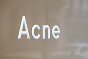 Acne sign in the shop window of high end fashion retailer Acne Studios in Mayfair on 5th March 2021 in London, England, United Kingdom.