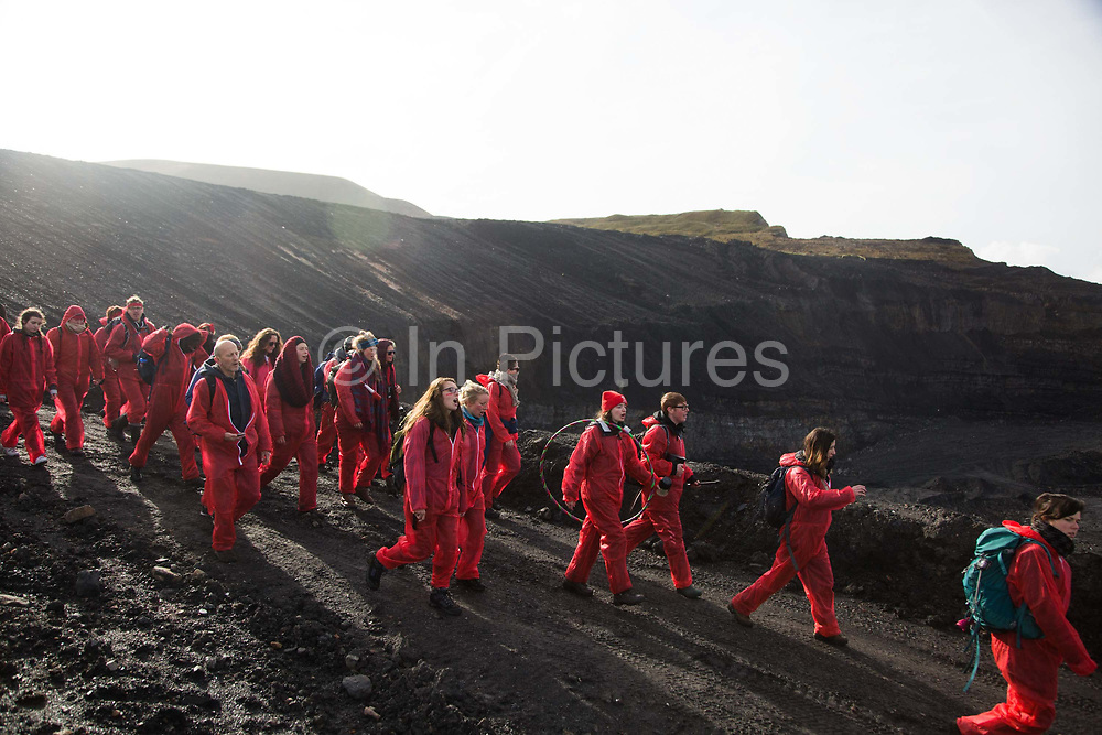 Hundreds of environmental activists stopping the open cast coal mine Ffos-y-Fran near Merthyr Tydfil, Wales from operating May 3rd 2016. Unchallenged by security the activists enter the mine which is not in operation and empty for any other activity. The activists from Reclaim the Power wants the mine shut down and a moratorium on all future open coal mining in Wales. The group Reclaim the Power had set up camp near by and had over three days prepared the action and up to 300 activists all dressed in red went into the mine in the early morning. The activist were plit in three groups and carried various props signifying the red line in the sand, initially drawn in Paris at the COP21. The mine is one of the largest open cast coal mines in the UK and is run by Miller Argent who have to date extracted 5million tons of coal. The activists entered the mine unchallenged by any security or police and the protest went on peacefully till mid afternoon with no arrests made.  Open coal mining is hugely damaging to the local environment and  contributing to global climate change.