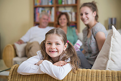 Portrait of grandparents and granddaughters sitting on couch, smiling