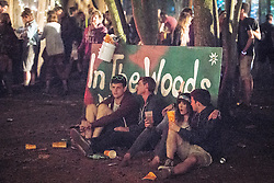 """© Licensed to London News Pictures . 22/07/2013 . Suffolk , UK . People sit on the ground by the """" In the Woods """" stage . Revellers enjoy the final night of the Latitude Festival . The Latitude music and culture festival in Henham Park , Southwold . Photo credit : Joel Goodman/LNP"""