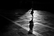 A lady wearing a hooded parka stands in St Mark's Square in Venice, Italy.