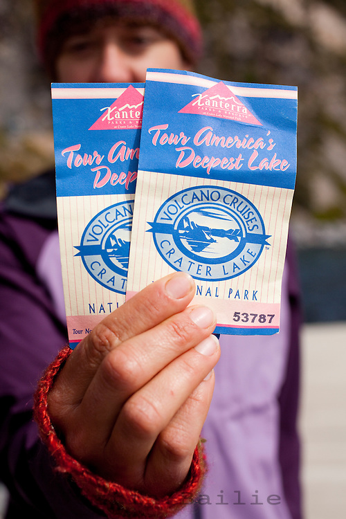 Young woman holding tickets for the boat tour of Crater Lake National Park, OR.