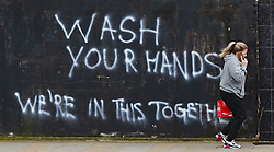 A woman walks past graffiti calling on people to wash their hands during the Covid-19 crisis in East Belfast.