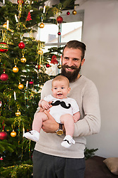 Father with son beside Christmas tree