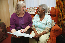 Professional visiting elderly woman at home......................................